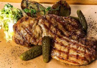 Gratar de muschiulet de porc marinat servit cu muraturi